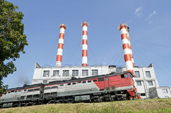 Locomotive moves against industrial building Royalty Free Stock Photography