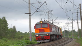 Locomotive moving in the countryside. Locomotive engine turning and passing by in rural area. Rail tracks among the green trees and electric poles stock video footage