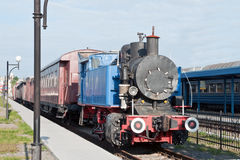 Locomotive pulls a train. Locomotive with a train leaves the station Stock Images