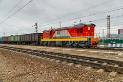 The locomotive pulls the wagons with a load. stock photo