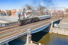 Locomotive retro steam with a passenger carriage passes over a bridge over a canal river in the historic part of the city royalty free stock photography