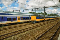Locomotive stop on train station and other train passing by in cloudy day at Weesp. Weesp, northern Netherlands - June 26, 2017. Locomotive stop on train Royalty Free Stock Photo