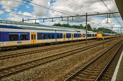 Locomotive stop on train station and other train passing by in cloudy day at Weesp. Weesp, northern Netherlands - June 26, 2017. Locomotive stop on train Royalty Free Stock Image