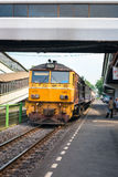 Locomotive with train arrives at railway station in Thailand. Dong Mueang, Thailand - 21 Nov 2013: Yellow locomotive with train arrives at railway station with Royalty Free Stock Photo