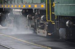 Locomotive train engine with smoke on railroad tracks Royalty Free Stock Image