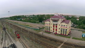 The locomotive travels over paths on the background of the station building. Railway station filmed on quadrocopter stock video footage