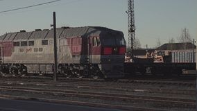 A locomotive without wagons rides past the station stock video footage