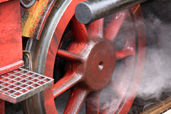 Locomotive Wheel. Steam gushing out near the red wheel of an old locomotive stock photos