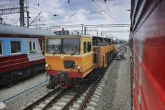 Locomotora en vías ferroviarias entre los trenes de pasajeros Imagen de archivo