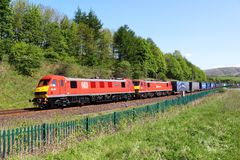 Locomotoras eléctricas rojas con el tren del envase Fotos de archivo libres de regalías