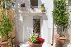 LOCOROTONDO. ITALY - APRIL 15, 2017 - A detail of walls and doors with colorful flowers and artworks in the picturesque little village in south Italy, famous Royalty Free Stock Photo