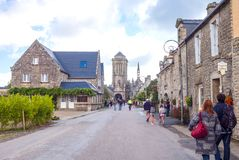 Landscapes and architectures of Brittany. Locronan, France - August 10, 2017: People in the main street with the St Ronan church in the background Stock Photos