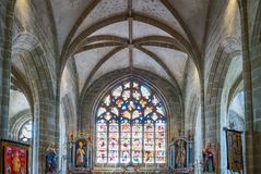 Landscapes and architectures of Brittany. Locronan, France - August 10, 2017: Statues of Saints and large staine glass window in the nave of the St Ronan church Royalty Free Stock Images