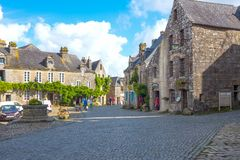 Landscapes and architectures of Brittany. Locronan, France - August 10, 2017: The traditional medieval houses of Town Hall square Royalty Free Stock Photo
