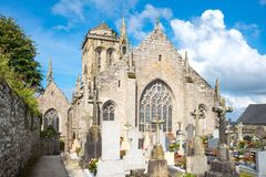 Landscapes and architectures of Brittany. Locronan, France - August 10, 2017: View of the apse of the St Ronan church with the cemetery in the foreground Stock Photo
