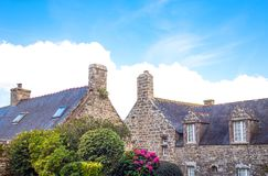 Landscapes and architectures of Brittany. Locronan, France, view of the traditional medieval houses in Charettes street with flowers in the foreground Royalty Free Stock Photo