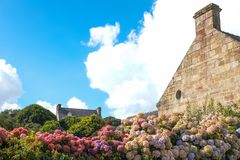 Landscapes and architectures of Brittany. Locronan, France, view of the traditional medieval houses in Lann street with flowers in the foreground Stock Photography