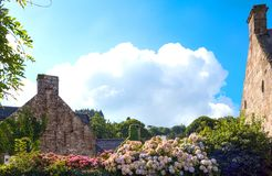 Landscapes and architectures of Brittany. Locronan, France, view of the traditional medieval houses in Laun street with flowers in the foreground Royalty Free Stock Photo