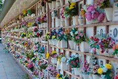 Loculi de um cemitério com muitas flores plásticas coloridas imagens de stock