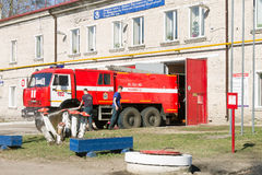 LODEYNOJE POLE, RUSSIA - MAY 2TH, 2016: Unidentified firefighters washing their fire truck next to the garage Stock Images