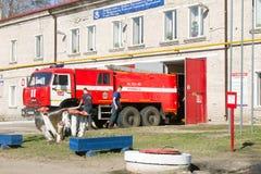 LODEYNOJE słup, ROSJA - MAY 2TH, 2016: Niezidentyfikowani strażacy myje ich samochód strażackiego obok garażu Obrazy Stock