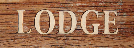 Lodge. The term lodge on a rustic wooden board Stock Image