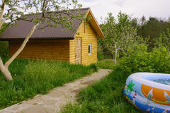 Lodge in garden. Small wooden house surrounded by green garden.Near the pool filled with water Stock Photos