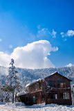 Lodge in snowy mountains. Scenic view of wooden or timber lodge or house with snowy forested mountains and blue sky background, Kartepe, Marmara, Turkey Stock Image