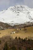 Lodges in glades under snowy rocky slopes of Arera peak, Italy Royalty Free Stock Photography