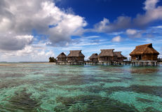 Lodges over transparent quiet sea water- tropical paradise, Maldives Stock Photo