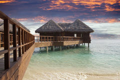 Lodges over water at the time sunset. Maldives. Stock Image
