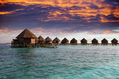 Lodges over water at the time sunset. Maldives. Royalty Free Stock Photo
