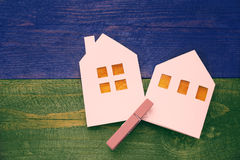 Lodges from white paper on a wooden background. Symbol of summer and spring. Stock Photo