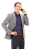 Lodlinjeskott av den unga mannen som talar på telefonen Royaltyfria Bilder