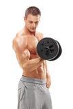 Lodlinjeskott av en manlig idrottsman nen som övar med en vikt Fotografering för Bildbyråer