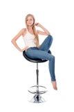 Lodlinjeskott av en ung härlig lång haired kvinnaplacering på en kontors- eller stångstol som isoleras på vit bakgrund royaltyfri bild