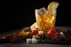 Lodowa herbata w szkle na czarnym talerzu z ciastkami, cukierkami i owoc na czarnym tle, obrazy royalty free