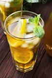 Lodowa herbata z cytryną i mennicą na drewnianym tle Fotografia Stock
