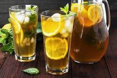 Lodowa herbata z cytryną i mennicą na drewnianym tle Obrazy Stock