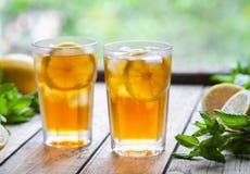 Lodowa herbata z cytryna plasterkami i mennica na drewnianym stole z widokiem tarasu Zamyka w górę lato napoju Fotografia Stock
