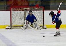 Lodowy gracz w hokeja strzela krążek hokojowego przy siecią fotografia royalty free