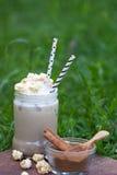 Lodowy kakao z cynamonem i batożącą śmietanką ozdabiał z karmelu popkornem Fotografia Royalty Free