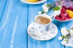 Lody różni kolory na błękitnym tle Malinki i mango Wystrój kwiaty i ranek kawa Bezpłatna przestrzeń dla fotografia stock