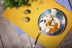 Lody z pęcherzycą i wysuszonymi owoc na talerzu na żółtym płótnie i Napój blisko deseru z herbacianą łyżką obraz stock