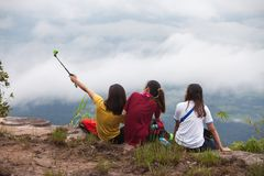 Loei ,THAILAND - October 2, 2017 :Women Traveler take photo her. And his friends by action camera at view point on Phukardueng peak Royalty Free Stock Images