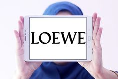 LOEWE fashion brand logo. Logo of LOEWE fashion brand on samsung tablet holded by arab muslim woman. LOEWE is a Spanish luxury fashion house based in Madrid and stock images