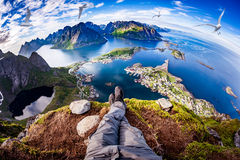 Lofoten archipelago Fisheye lens. First person perspective shot from a hiker sitting at the edge of a cliff at Lofoten is an archipelago in the county of stock photography