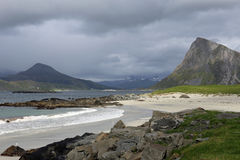 Lofoten beach and mountains on a rainy day. Landscape with sandy beach, fjord and mountains on Lofoten islands, Norway Royalty Free Stock Image