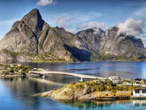 Lofoten Islands Reine Norway. The bridge connecting the two islands in fjord. In the background is scenery of high mountains. Lofoten islands - Norway Royalty Free Stock Images