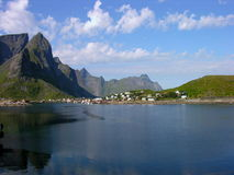 Lofoten lagoon. Mountain overhanging little Lofoten village by the sea, sightseeing in norway Stock Photos